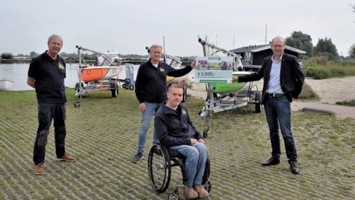 Voorzitter Joop Atsma van de TVM foundation overhandigt de cheque aan Zeilen Zonder Beperking.