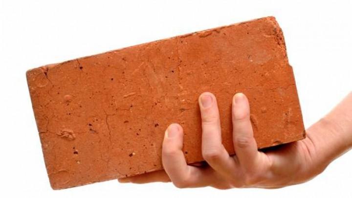 Autoruit met baksteen ingeslagen