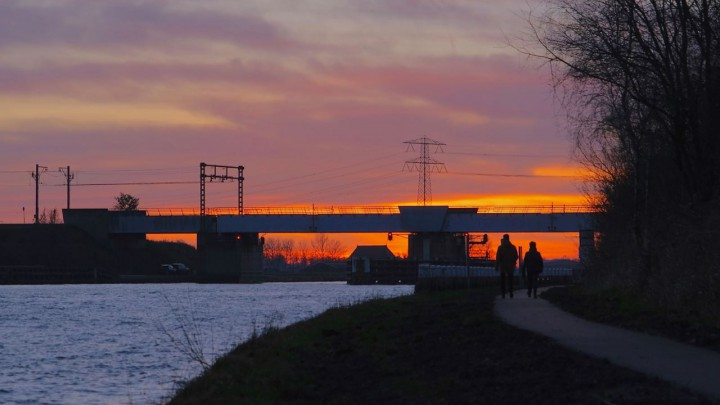 Zon gaat onder achter spoorbrug