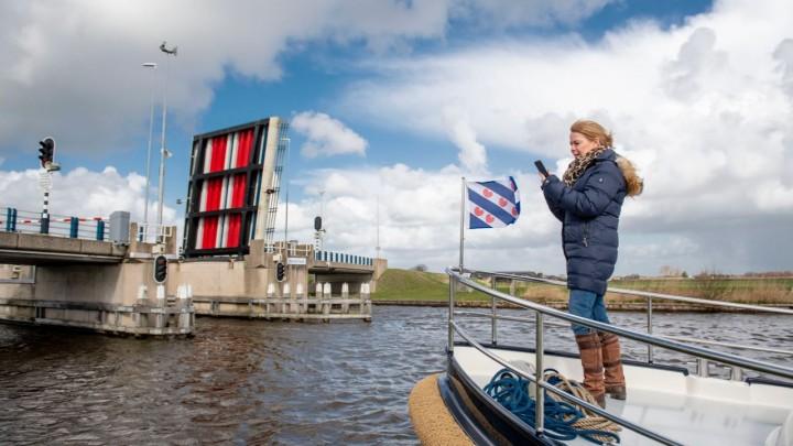 Gedeputeerde Avine Fokkens–Kelder opent de brug bij Langweer met de app.