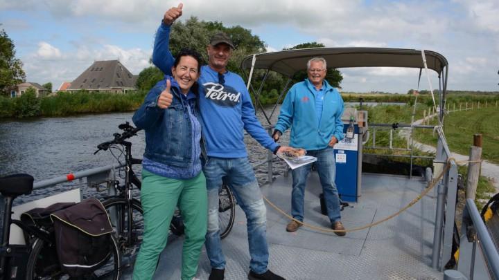 Cora de Visser en Ron van der Eng zijn blij verrast. Pontschipper Jelle van der Schaaf kijkt lachend toe.