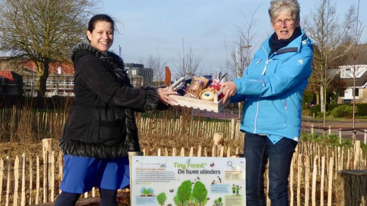 Hinke Volbeda (rechts) van Grou 2030 reikt het kerstpakket uit aan Johanna Popkema.